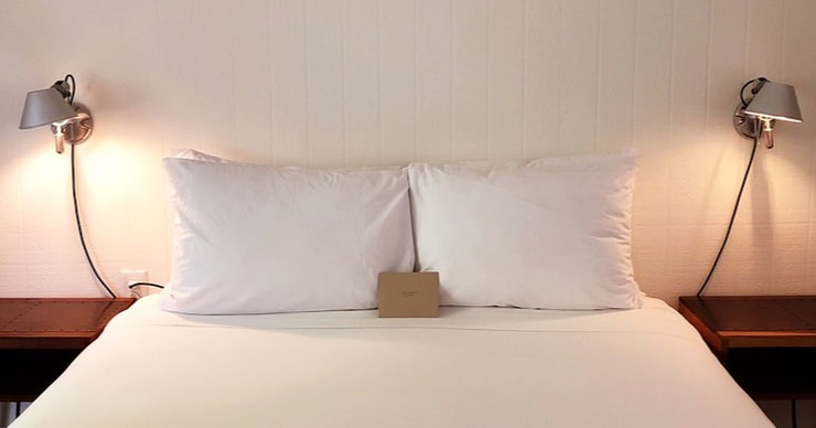 Photo of a bed with two lights on either side to represent the relationship between sleep and mental health. Our psychologists help individuals in the Tampa area get better sleep.