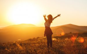 A woman stands on a hilltop with arms outstretched as she enjoys the setting sun. This could symbolize the freedom felt after completing EMDR therapy. We offer EMDR therapy in Tampa, FL. Get in touch with an EMDR therapist, and begin overcoming past trauma.
