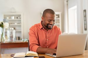 A man smiles as he types on his laptop resting on the kitchen counter. Online therapy in Florida can provide support from the comfort of home. Contact an online therapist to learn more about online anxiety treatment, online trauma therapy, and other services.