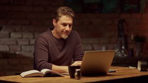 A man sits at his kitchen table in front of his laptop as he smiles. This could represent meeting with an online therapist in Florida. Contact us to learn about online EMDR therapy, online therapy, and other services.