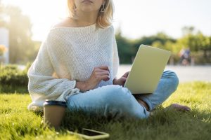 A woman sits cross-legged in the grass with a laptop. This could represent online therapy in Florida and the ability to meet with an online therapist anywhere. Learn more about online trauma therapy and other services today.