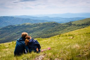 A couple sit together as they look out over the mountain range before them. Couples therapy in Tampa, FL can help cultivate stronger bonds. Contact a marriage counselor in Tampa, FL for support with marriage counseling and other services. 33609   33704   337703